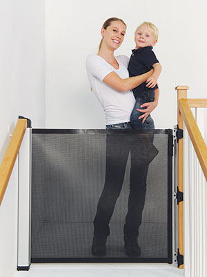 KiddyGuard Avant mum with Boy on top of stairs closed gate Bannisters