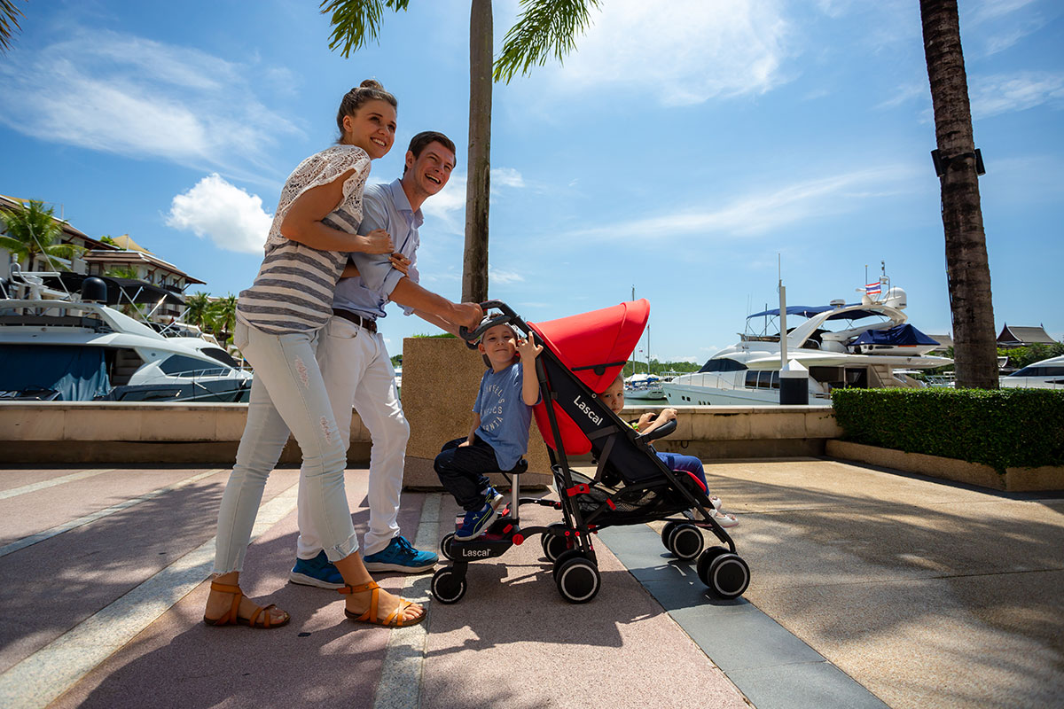 BuggyBoard Maxi+, m1 Buggy parents with two kids walking along the harbour 01