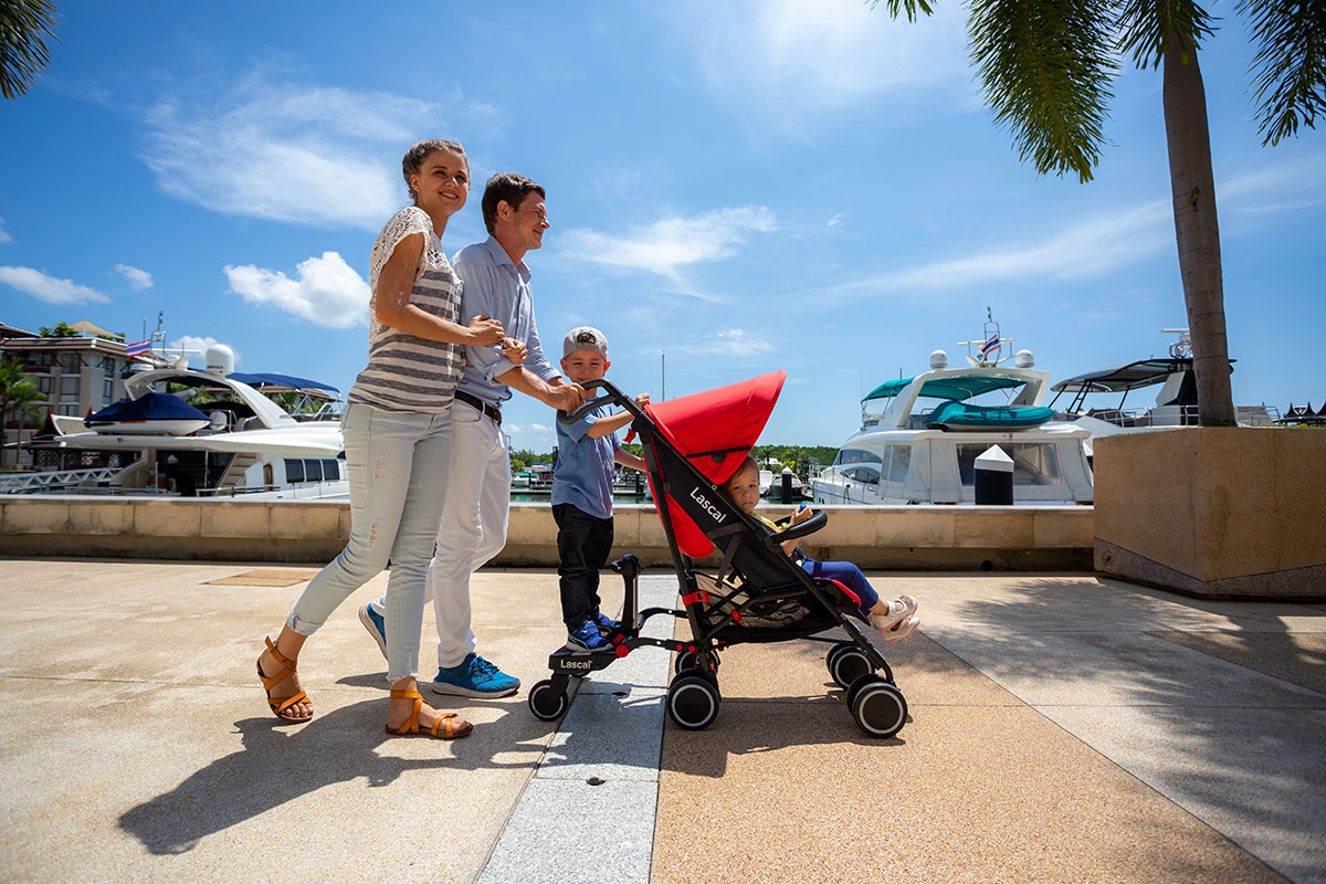 BuggyBoard Maxi+, m1 Buggy parents with two kids walking along the harbour 02